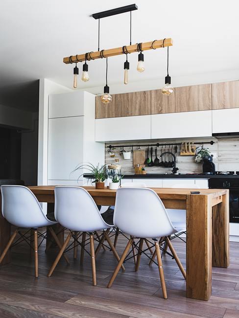 Cocina americana de estilo industrial con mesa grande de madera y sillas blancas