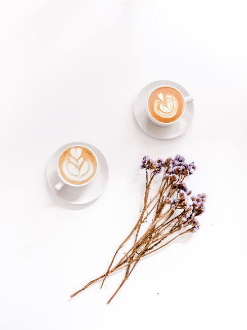 vue du haut sur deux tasses de café au lait avec fleurs séchées posés à côté