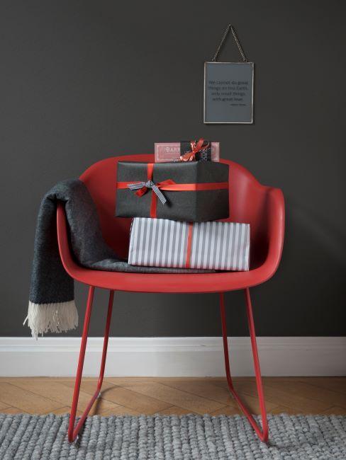 chaise rouge avec un plaid et deux cadeaux emballes, poses dessus