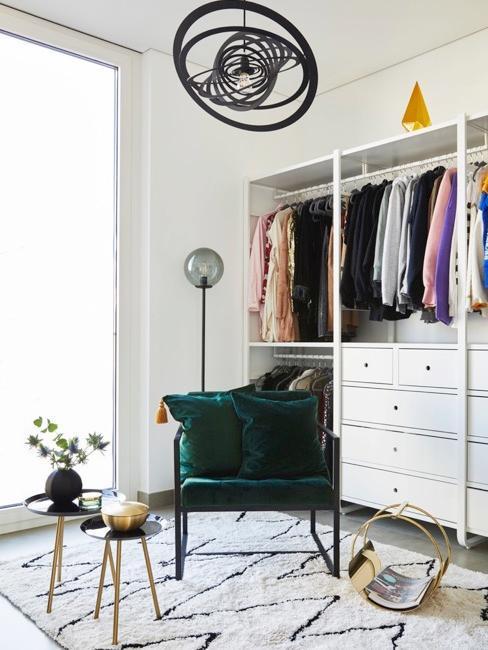 Chambre avec grand dressing, fauteuil vert sur tapis noir et blanc et grande fenêtre