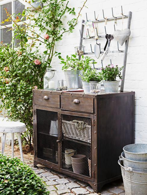 vieille commode contre un mur extérieur, décorée des plantes dans des pots blancs