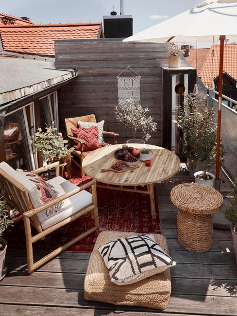 Petite terrasse avec des chaises et tables en bois ainsi qu'un pouf