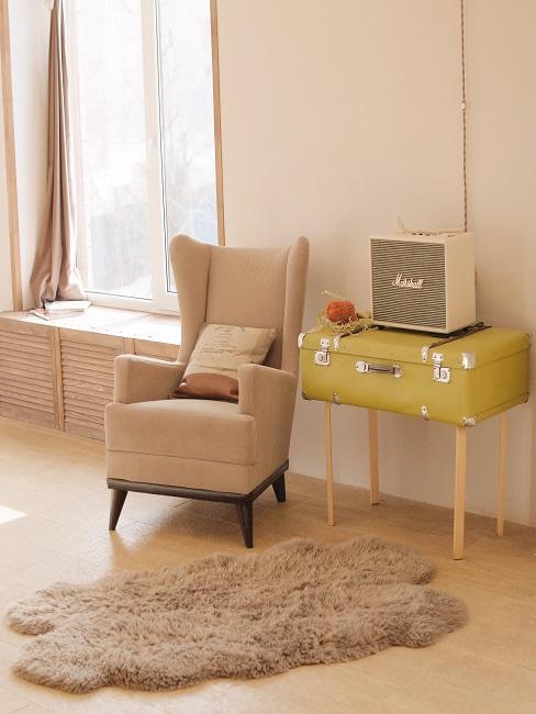 Salon avec fauteuil beige et meuble jaune, tapis en fausse fourrure