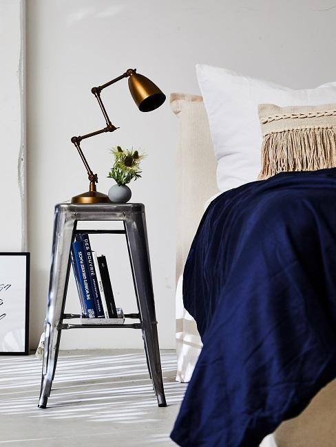 Couvre-lit en velours bleu foncé et lampe à poser industrielle