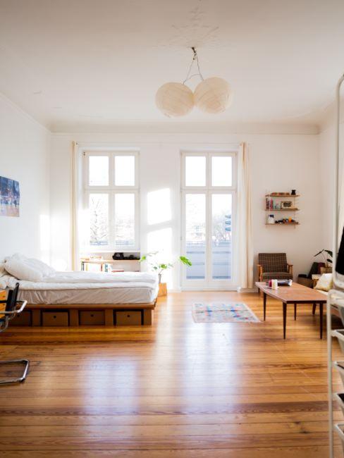 grand espace ouvert, parquet, planchers en bois, grandes fenetres, murs blancs, lumineux, chambre a coucher et coin salon dans la meme piece