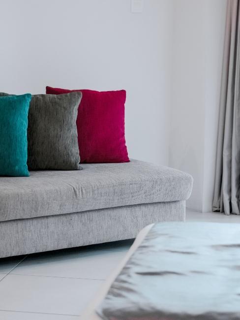 Méridienne grise avec trois coussins décoratifs en velours de couleurs différentes