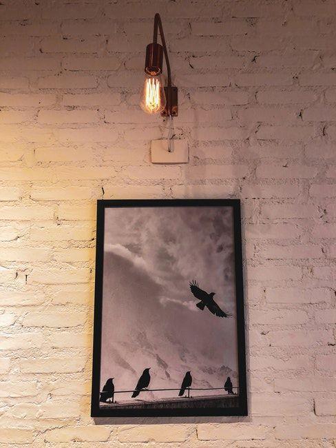 Applique murale illuminant un tableau accroché au mur blanc