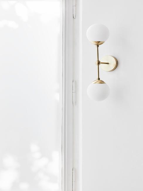Mur blanc avec applique murale dorée et deux lampes blanches rondes