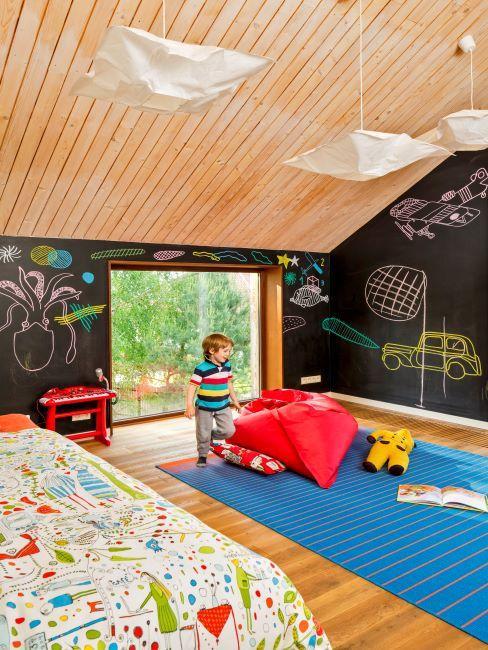Petit garçon dans sa grande salle de jeu aux murs décorés de tableaux noirs sur lesquels il dessine, d'un grand pouf rouge au milieu de la pièce et d'un tapis bleu