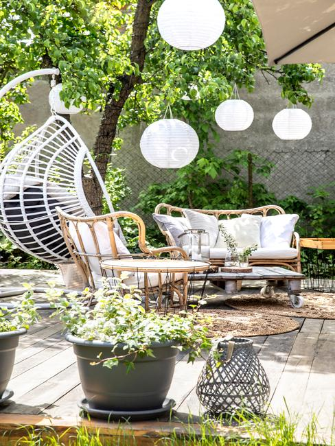 Terasse avec fauteuil suspendu blanc, laternes d'extérieur et plantes en pots