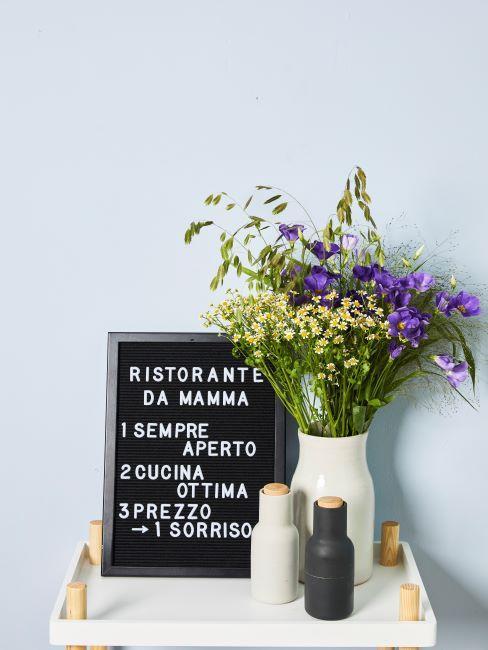 Commode blanche avec moulins a epices, bouquet de fleurs dans un vase et tableau en ardoise