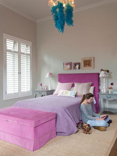 une fille adolescente assise par terre a regarder son tablett dans sa chambre claire avec lit rose vif