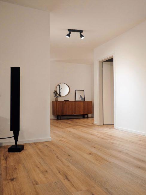grand sejour a decoration zen minimaliste, sol en bois et commode avec miroir mural