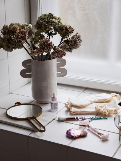 rebord de fenetre avec accessoires de maquillage disperses, miroir et fleurs sechees dans un vase