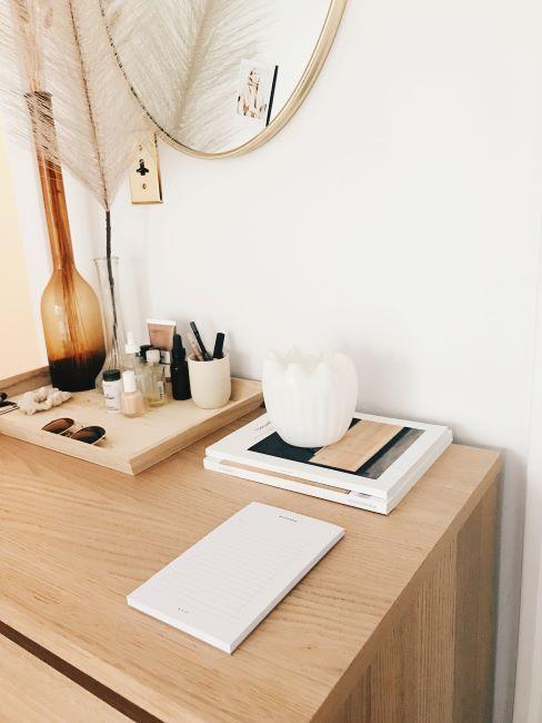 commode en bois, magazines, vase blanc, plateau en bois avec maquillage et vases en verre teinté
