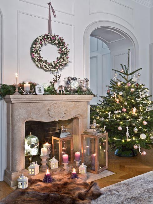 salon decoration de noel, sapin de noel, guirlande de noel, lanternes avec bougies allumees, cheminee decoree des branches de sapin