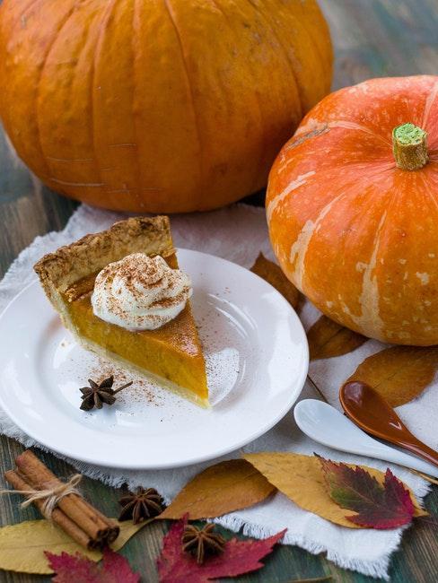 deux citrouilles et un morceau de tarte au potiron sur une assiette a dessert blanche
