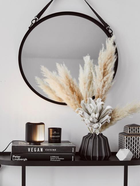 Zwarte keramische vaas met gedroogde bloemen en koffietafelboek op zwarte dressoir