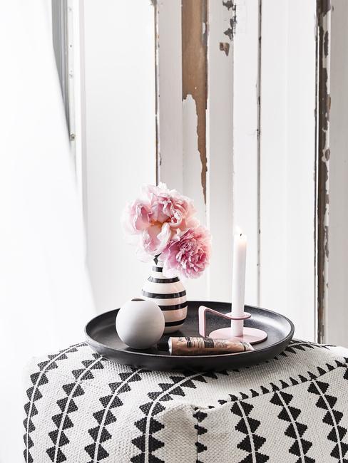 Witte poef met patroon met zwart decoratief dienblad met vaas uit keramiek met bloemen en kaars