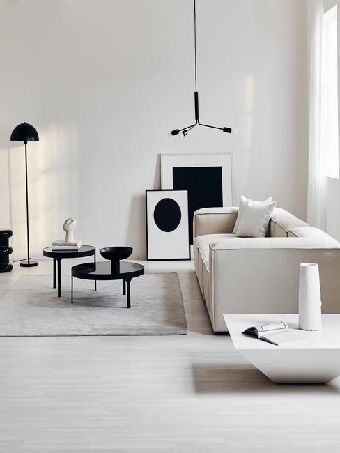 Een moderne woonkamer met witte zitbank met witte kussens en zwarte salontafels met decoraties en bijzettafel in betonlook