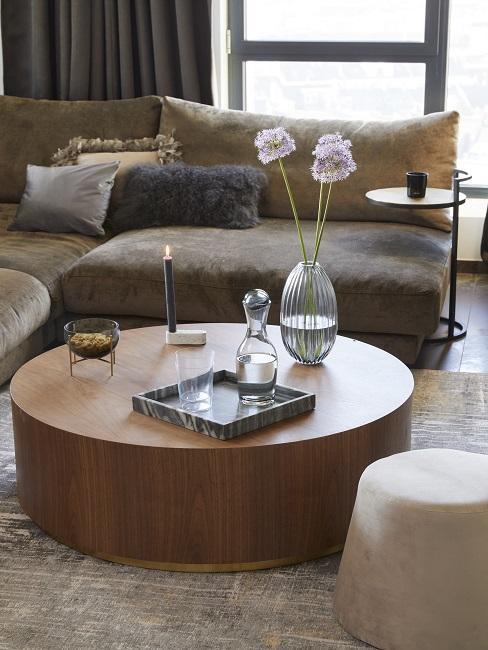 Woonkamer met bruin leren bank ronde salontafel en bruin vloerkleed
