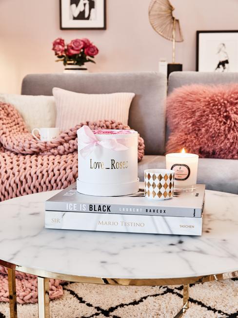 Een grijze bank met sierkussens en zachte chunky knit plaid naast een marmeren salontafel met koffietafelboek en geurkaars