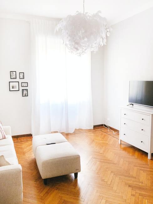 Lichte kamer met houten vloer en wit meubilair