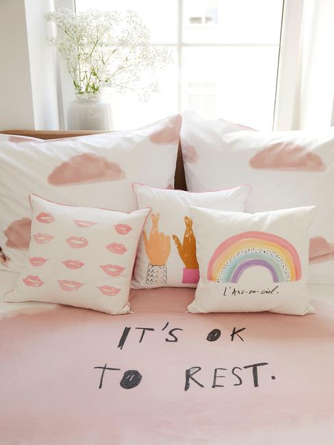 Babykamer decoratie: bed met roze beddengoed en veel kussens in pastelkleuren