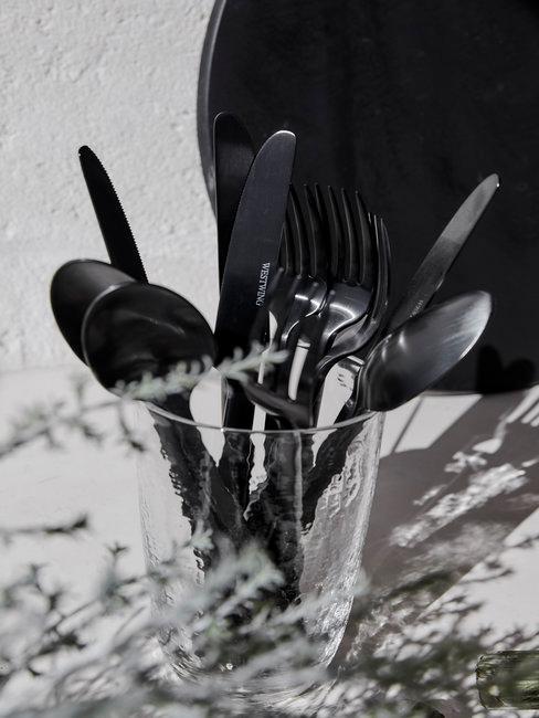 Zilver bestek in glas op aanrecht in zwart wit
