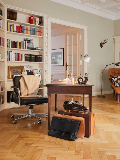Een woonkamer met houten bureau en witte boekenkast