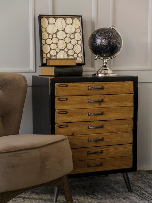 Close-up ladekast met wereldbol en boeken naast bruine fauteuil