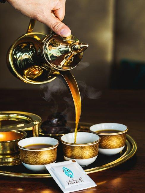 Suikerfeest Hand met gouden theepot met gouden schaal en wit met gouden theemokken op houten tafel