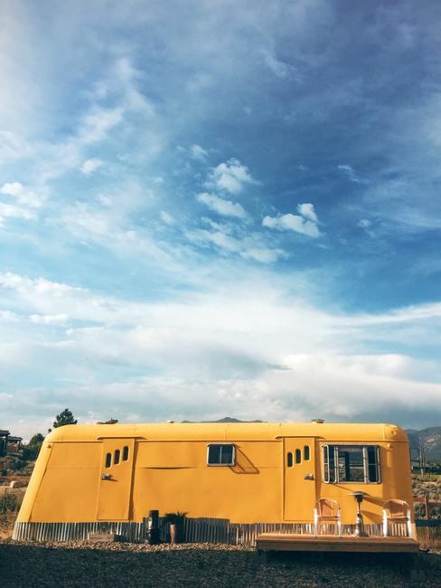 Gele vintage kemper in de natuur met blauwe hemel