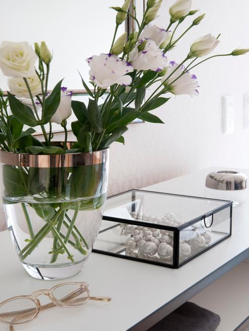 Boeket voorjaarsbloemen in een vaas naast glazen opbergdoos op witte sidetable bij het schrijven van de speech bruiloft