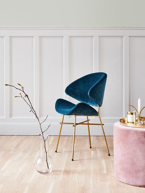 Witte lambriserig met licht houten vloer en petrol kleur velvet stoel