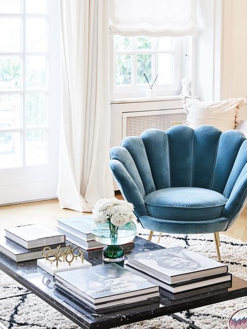 Lichte witte woonkamer met salontafel met koffieboeken en blauwe velvet stoel