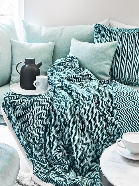 Turquoise bank met pleed an koffiekan met beker