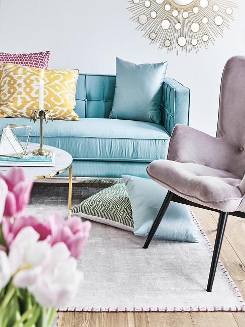 Woonkamer met turquoise bankstel en pastelkleuren accessoires en paarse stoel