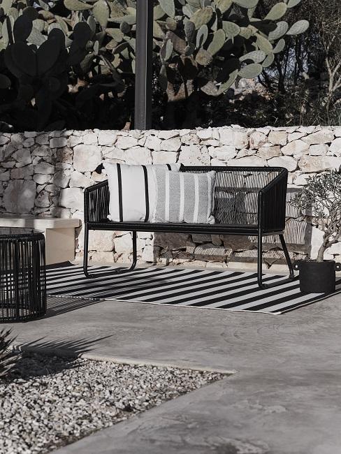 Tuinmeubels kunststof zwart voor een stenenmuur op een grijze vloer