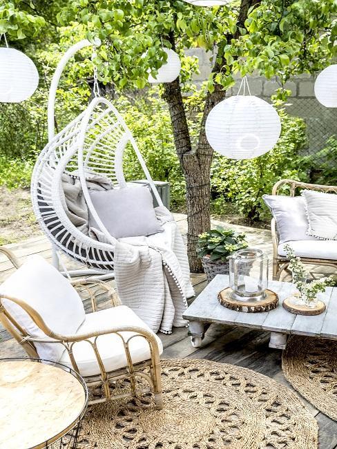 Witte tuinmeubels in groene tuin met bijzettafel