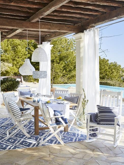 Mediterrane tuin onder pergola met witte houten tuinmeubel set op blauw vloerkleed
