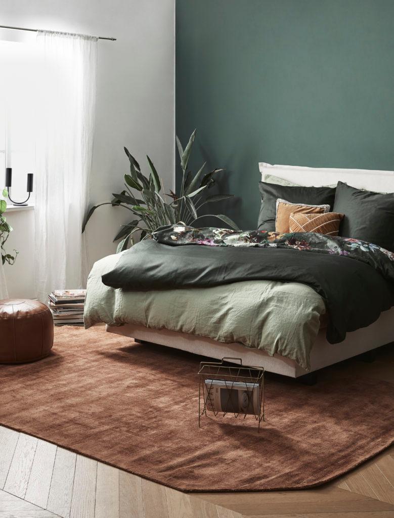 Donkergroene muur in slaakamer met groen bedlinnen en bruin vloerkleed