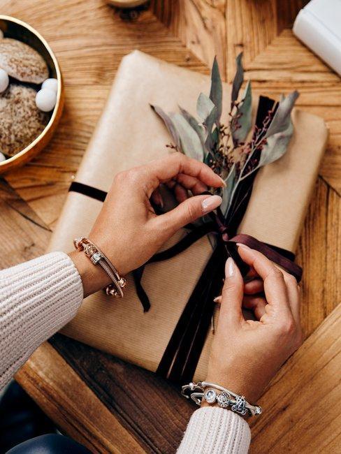 Cadeau verpakking met strik en handen op houten tafel