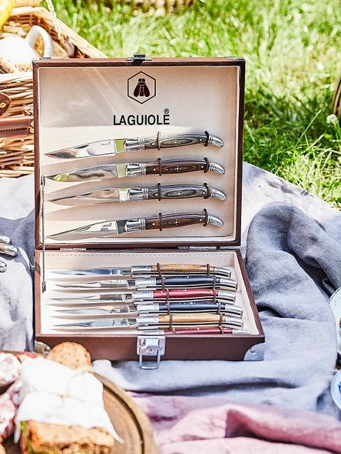 Een set messen als geschenk gelegd op een plaid in de tuin