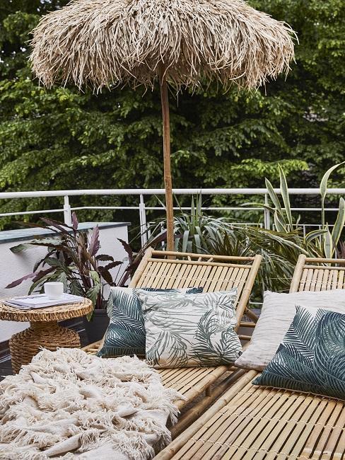 Ligstoelen van rotan met rieten parasol in tropische tuin
