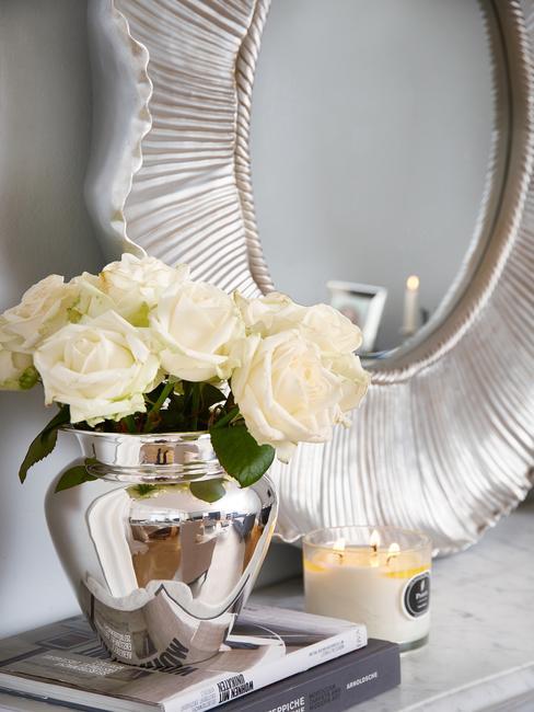 Een decoratieve spiegel op een grijze muur en een boeket rozen in een zilveren vaas