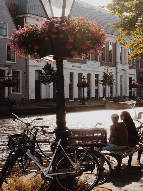 Fietsvakantie 2 fietsen geparkeerd op pleitjes met twee personen op een bankje met huizen op de achtergrond