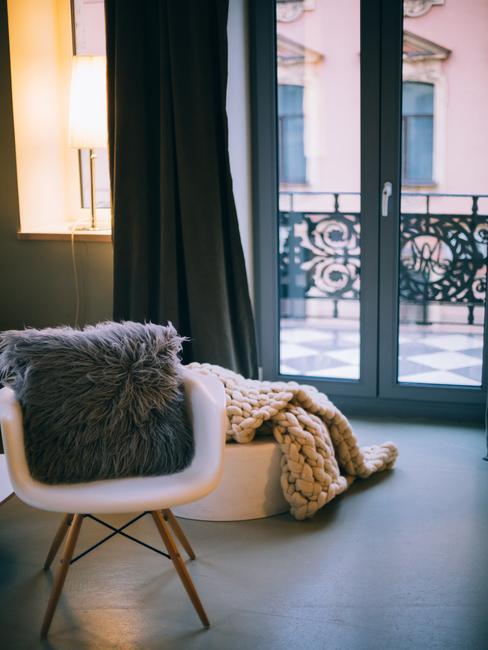 Woonkamer met een stoel met een sierkussen en een witte poef met plaid in een romantisch interieur