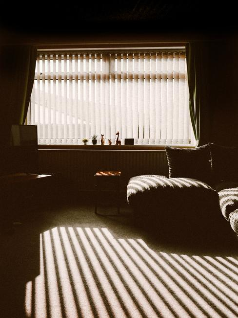 Een schemerige kamer met een poef en een bank