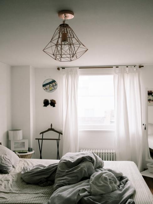 Een slaapkamer in wit en grijs met een onopgemaakt bed en een lang wit gordijn op het raam
